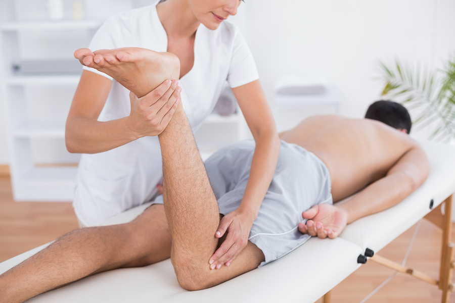 Physiotherapist doing leg massage to her patient in medical offi